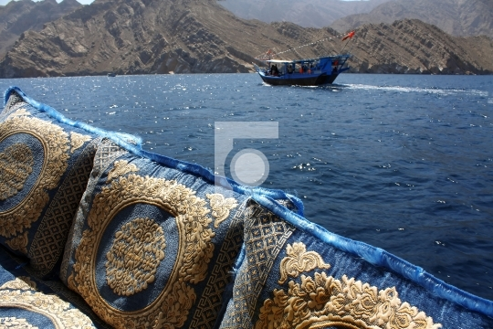 embroidered cushions and dhow cruise in oman waters