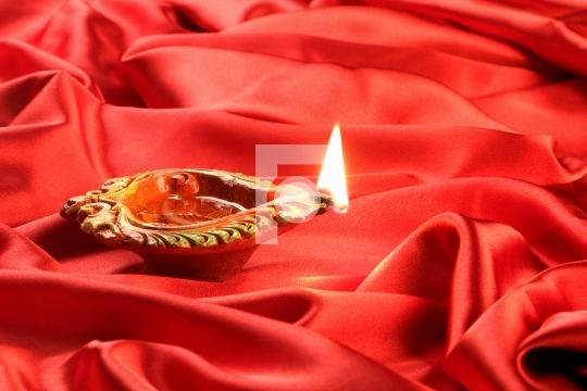 Handmade Diwali Clay Lamp on Red Satin Background