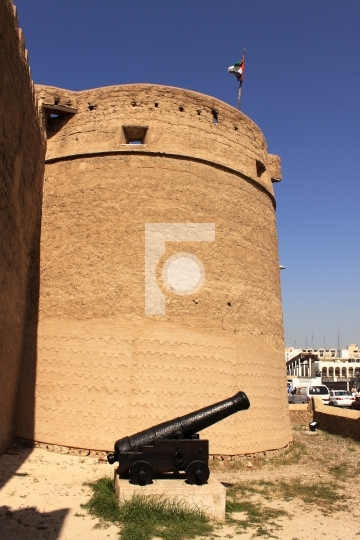 old fort and a antique cannon outside dubai museum, united arab