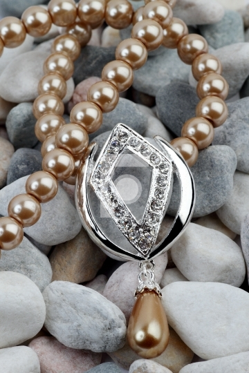 Pearl, diamond jewelery on stones background