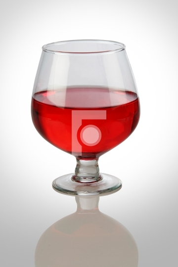 Red Wine Glass on White Reflective Background
