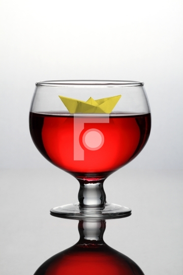 Red Wine Glass with a Paper Boat - Concept