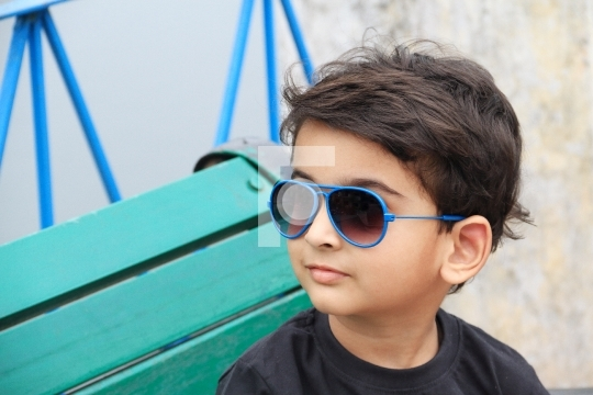 Smart Indian Toddler Boy with Sunglasses on a Bench