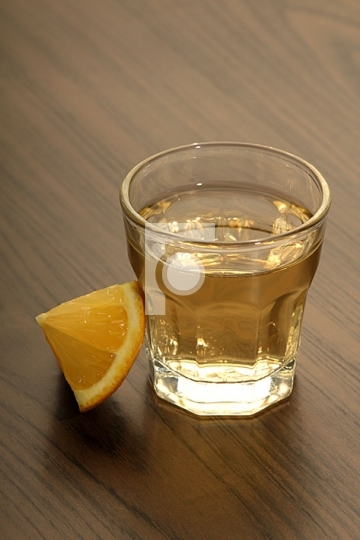Tequila shot with lemon on a wooden table