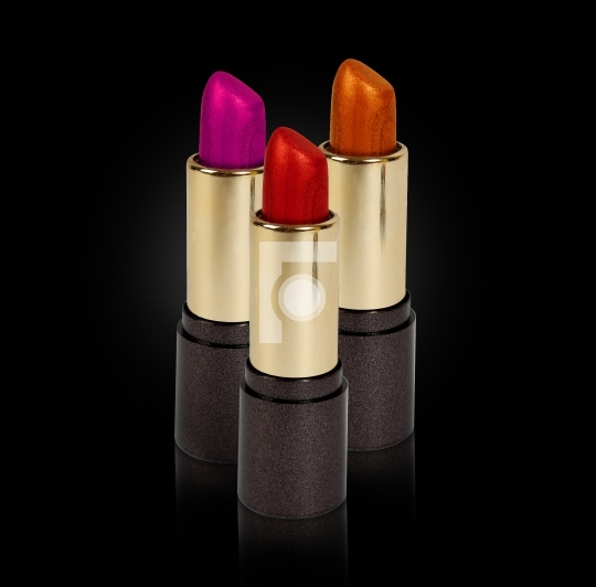 three colored lipsticks
